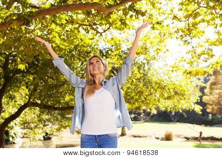 happy young woman with arms open under the trees