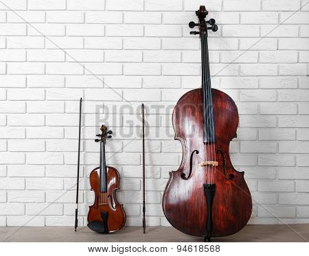 Cello and violin on bricks wall background