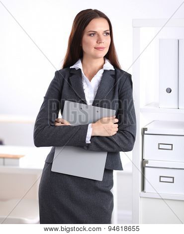 Attractive businesswoman standing near desk in the office
