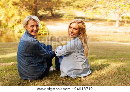 relaxed middle aged mother and daughter sitting outdoors