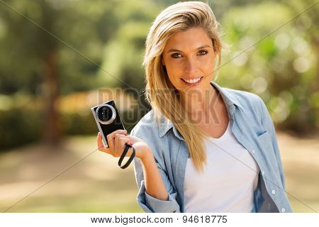 smiling young woman holding a camera outdoors
