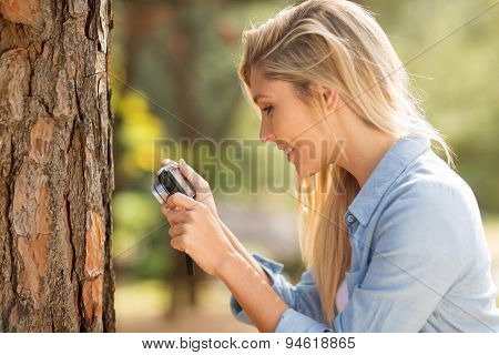 woman taking photo of tree stem closeup
