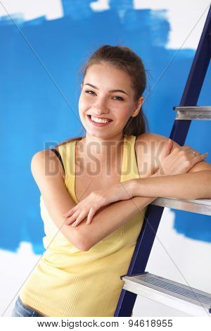 Beautiful young woman doing wall painting, standing near ladder.