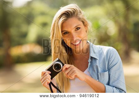 happy young woman holding a camera at the park