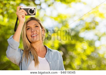 attractive young woman taking photos in forest