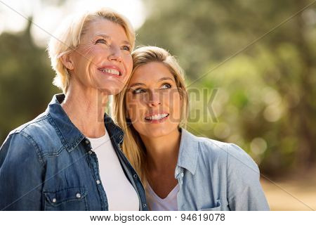 cheerful mother and daughter looking up