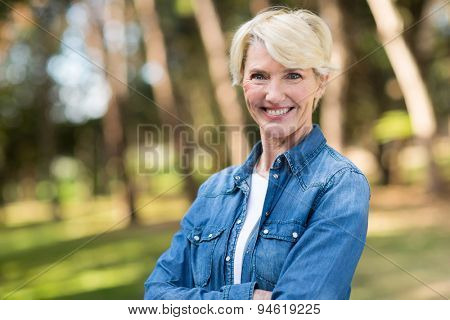 beautiful middle aged woman with arms folded outdoors