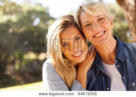 happy middle aged blond mother and adult daughter outdoors