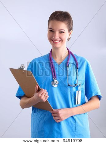 Smiling female doctor with a folder in uniform standing
