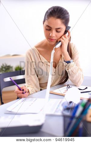 Young businesswoman sitting and talking on phone