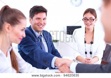 Business people shaking hands, finishing up a meeting, in office.