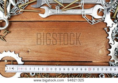 Screw nuts and wrenches frame, on wooden background