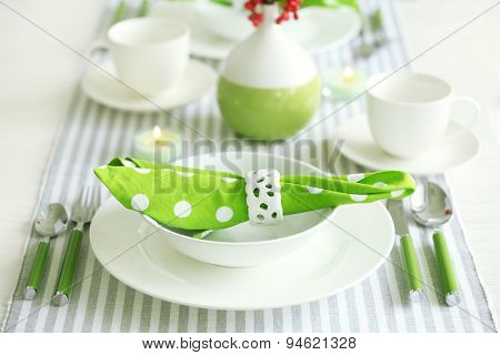 Beautiful holiday table setting in white and green color