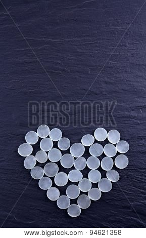 Decorative stones in heart shape on gray background