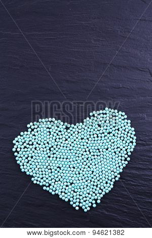 Colorful beads in heart shape on grey background