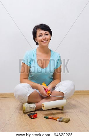 Young smiling woman with painting roller