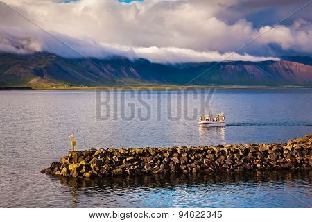 White fishing boat in the harbor pier fishing village Arnastapi. Sunset on the sea fjord in Iceland