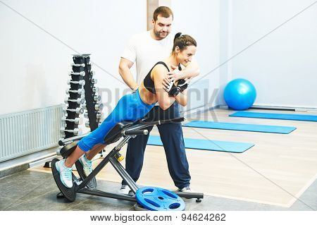 fitness and sport concept. personal coach trainer helps woman work out at a gym with heavy weight