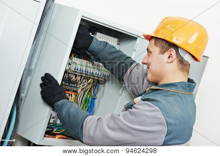Young adult electrician builder engineer screwing equipment in fuse box
