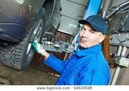 portrait of car mechanic worker before repairing suspension of lifted automobile at auto repair garage shop station
