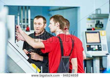 three industrial workers at cnc turning machine center in tool manufacture workshop