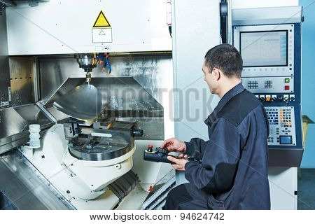 metalwork industry. worker operating cnc milling machine center in tool manufacture workshop