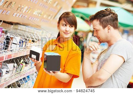 Young female assistant seller helps purchaser choosing lamp in hardware shopping mall supermarket