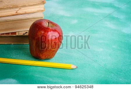 Stack of books with apple and sheet of paper with pencil on it. Isolated on green