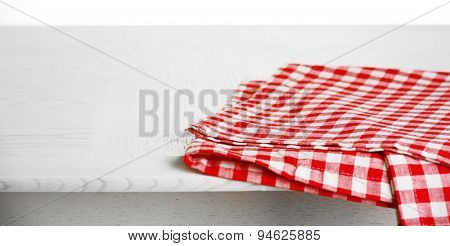 Wooden table with napkin isolated on white