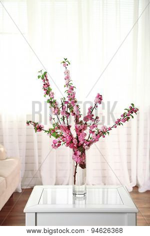 Spring bouquet in vase, on table, on home interior background