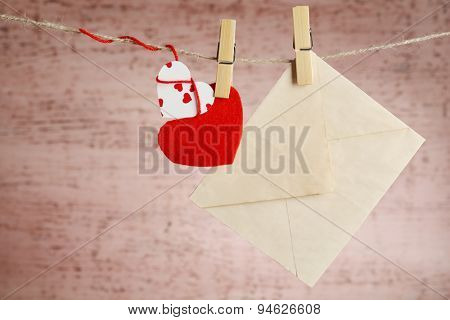 Bright hearts and envelope hanging on rope on wooden background