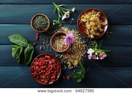Herbs, berries and flowers on color  wooden table background