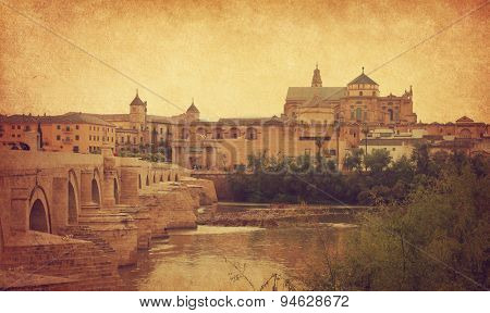 View of the Roman bridge and Cathedral of Cordoba, Spain.  Photo in retro style. Added paper texture.