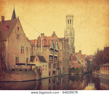 Bruges historic centre. The classic view from the Rozenhoedkaai. Belgium. Photo in retro style. Added paper texture.