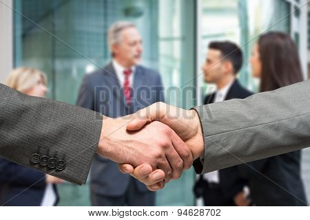 Business handshake. Business people talking in the background