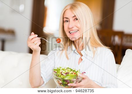 Portrait of a smiling woman eating an healthy salad in her living room