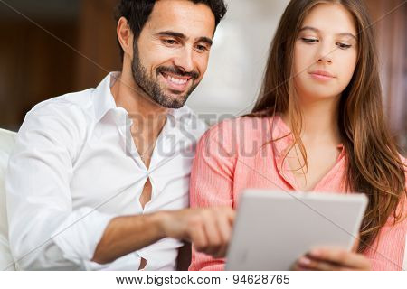 In love couple using a tablet computer in their living room