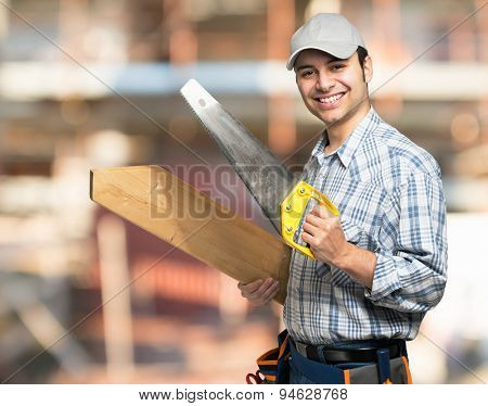 Portrait of a smiling carpenter holding a wood plank and a saw in a construction site