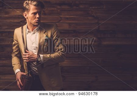 Stylish man wearing jacket in rural cottage interior