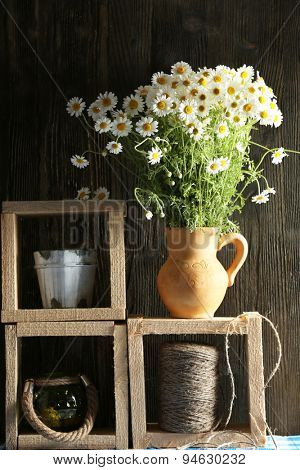 Beautiful bouquet of daisies in pitcher with twine on wooden background