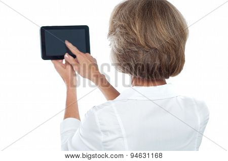 Mature Woman Using Tablet, From Back.