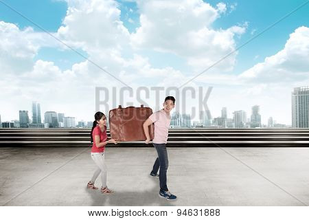 Young Couple Carry Baggage