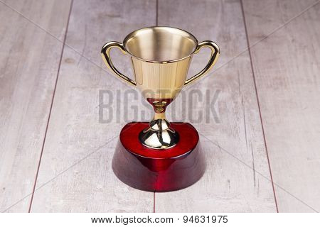 Golden trophy on wood background.
