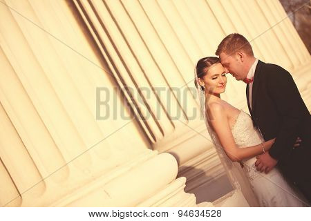 Bride And Groom Near Columns
