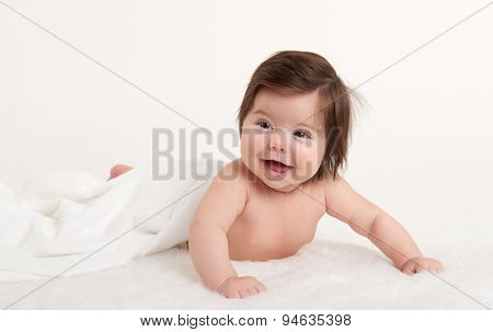 happy baby under towel on white background