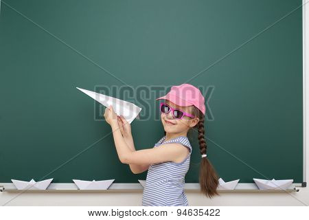Schoolgirl with origami plane near school board