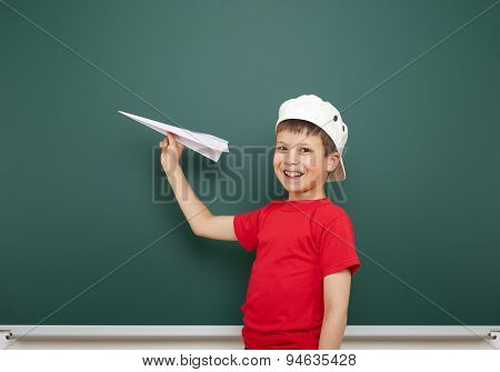 boy with origami toy near the school board