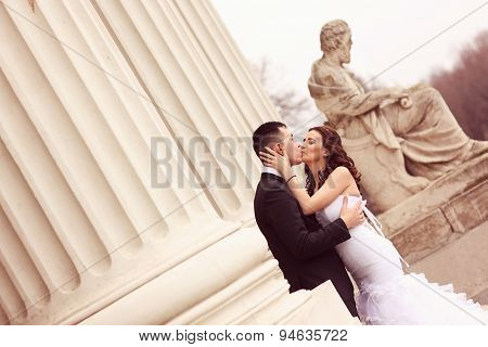 Bride And Groom Near White Columns