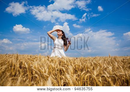 Happy young woman enjoying life in golden wheat field
