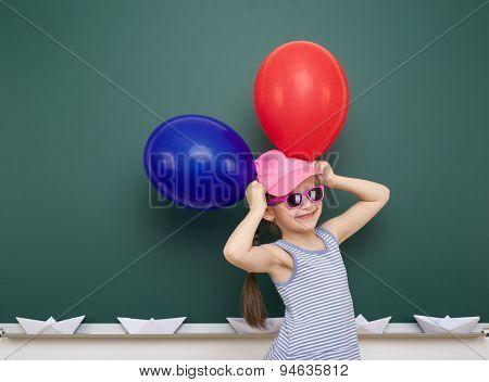 girl with balloon near the school board